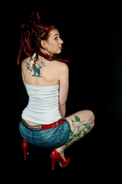 Tattooed model Eve, crouching